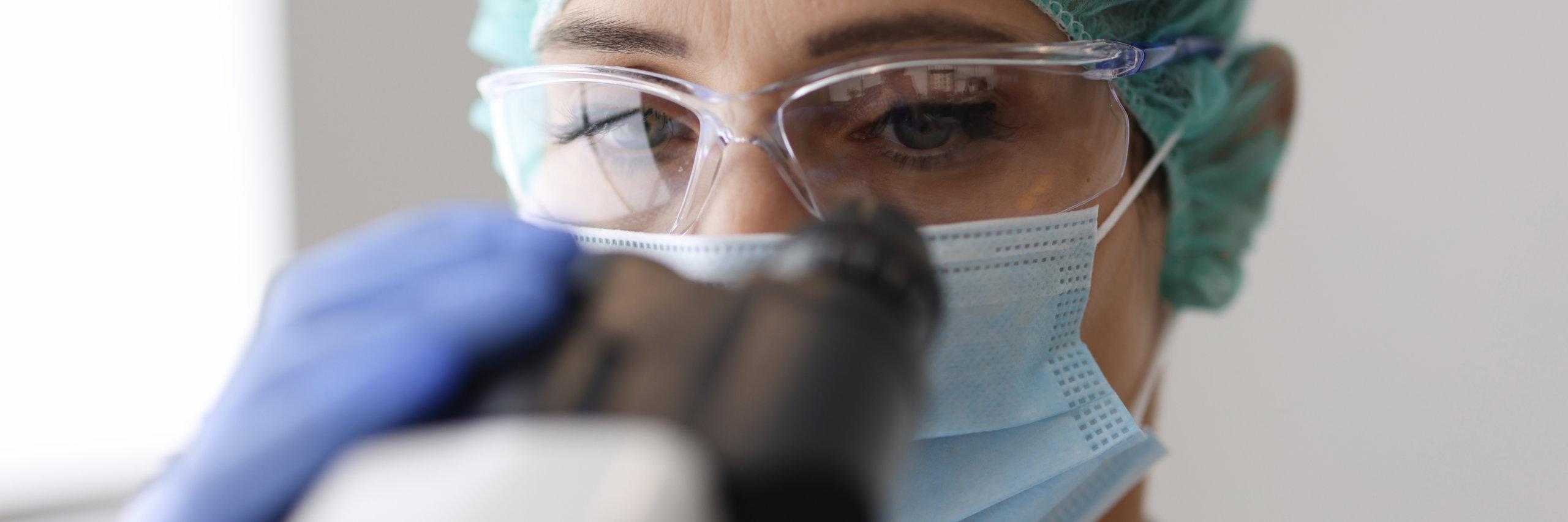 un soignant regardant dans un microscope