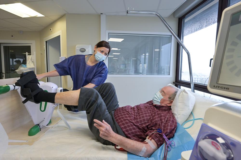 Soignant aidant un patient dans un service de dialyse